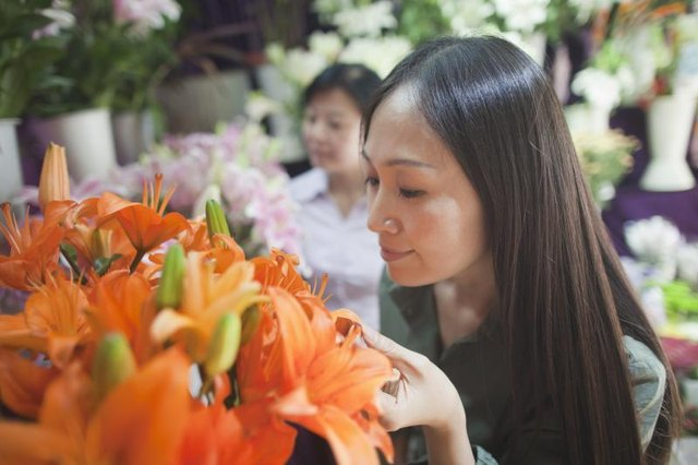 Woman smelling an orange bouquet of flowers at a shop.