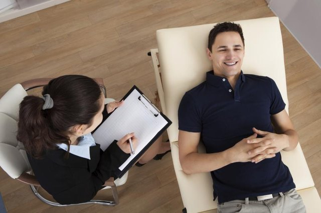 A high-angle view of a patient communicating with his therapist.