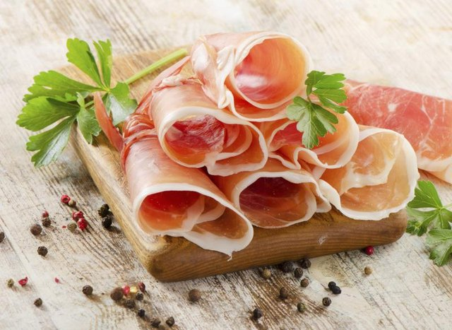 Sliced rolls of prosciutto on a wood serving tray.