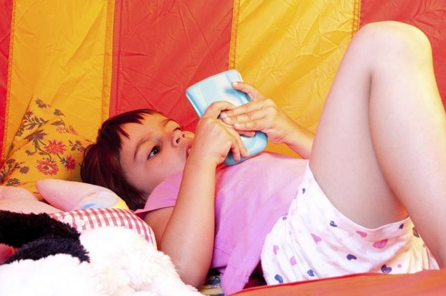 Young girl playing video games inside a tent.