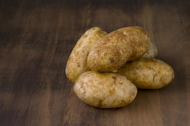 Pile of russet potatoes on tabletop.