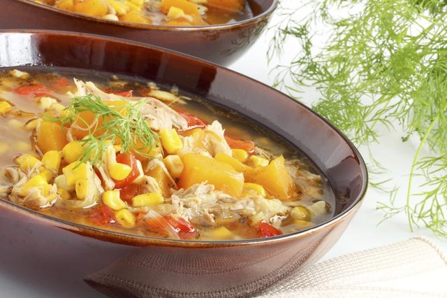 A bowl of chicken and corn in a broth.