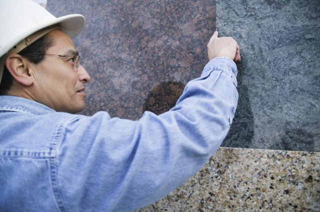 Man examining sheets of granite.
