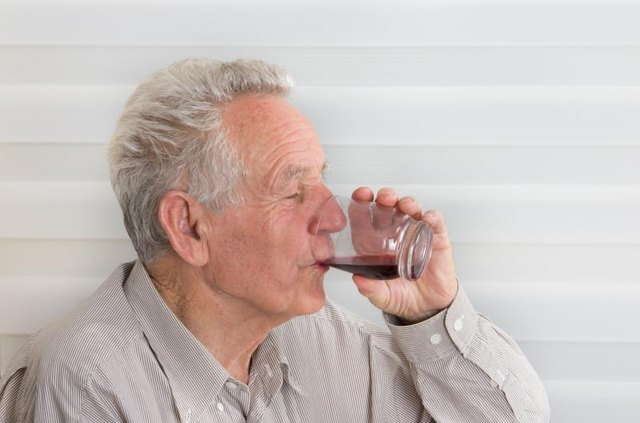 A man drinking a glass of cherry juice.