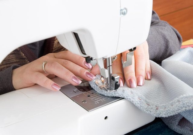 Hands using a sewing machine.