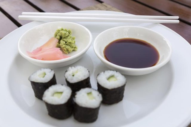 A sushi roll on a plate with soy sauce, wasabi and pickled ginger.