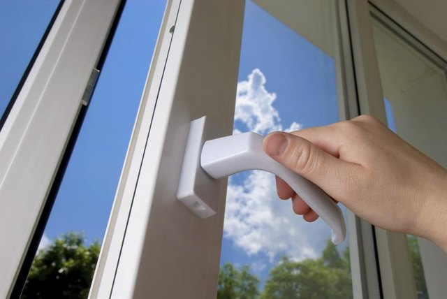 A hand opens a window, using a handle.