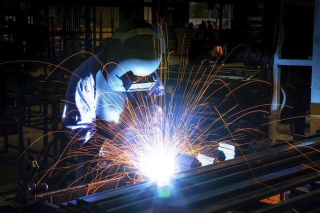 A welder works on a steal structure.