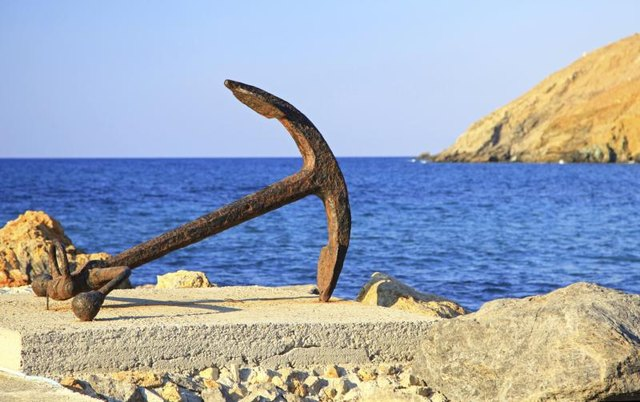 An old anchor laying on rocks next to the ocean.