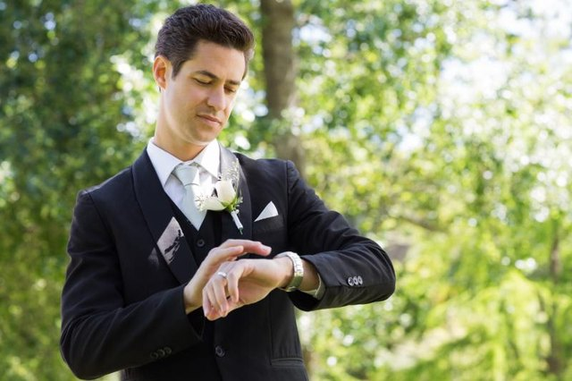 A groom is checking his watch.