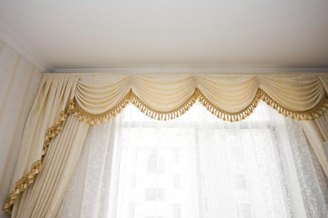 Floor length formal drapes with a tassled fringe over sheer curtains.