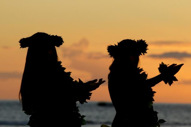 Silhouette of Hawaiian dancers at luau