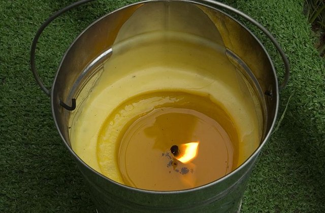 A lit citronella candle in a bucket burning outside.