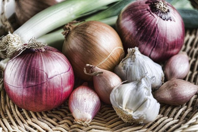 Garlic bulbs and an assortment of onions.