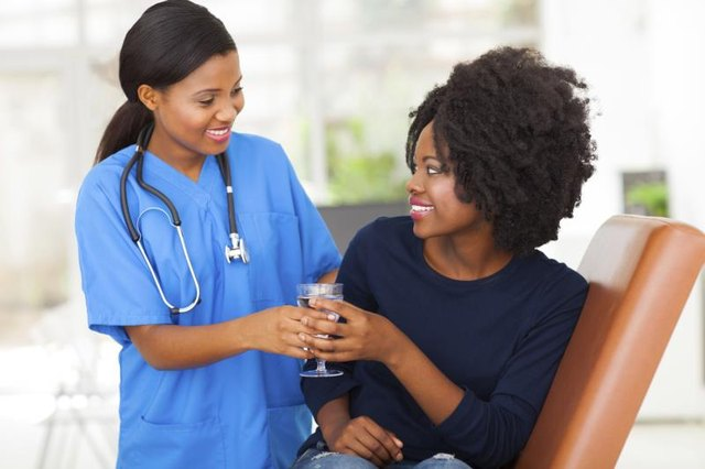 A medical assistant hands a patient a glass of water