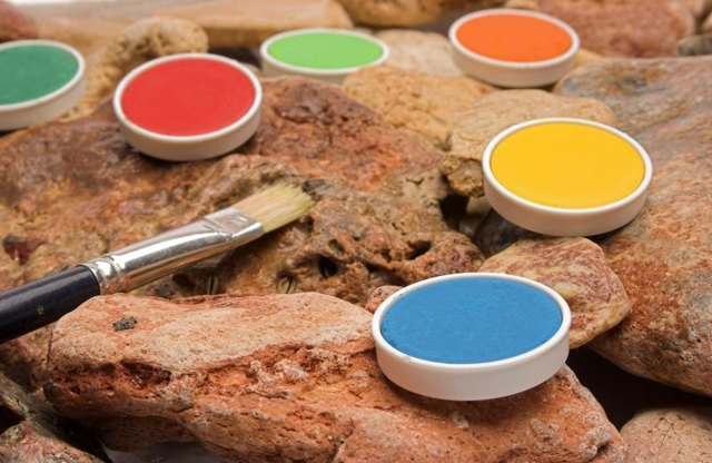 Colorful paint cells and a paintbrush on red rock.