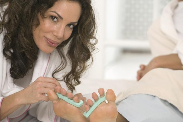 Cosmetologist giving pedicure to patient