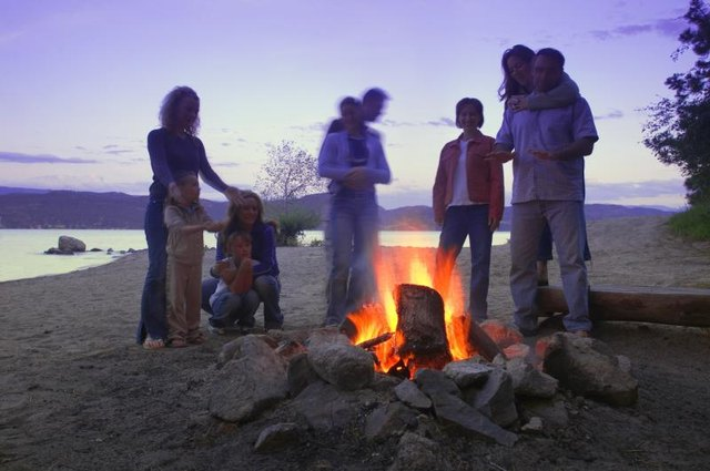 A family at a bonfire near the water.