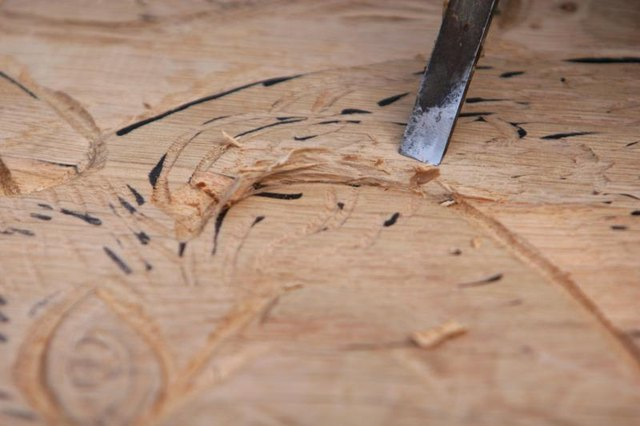 A chisel being used to carve a design.