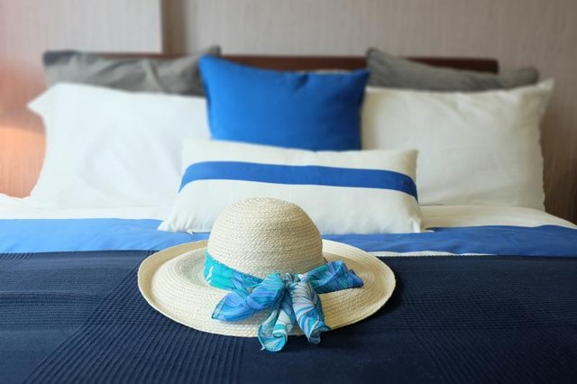 A close-up of a beach hat on a bed with various shades of blues.