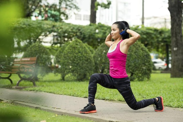 Woman practicing lunges outside.
