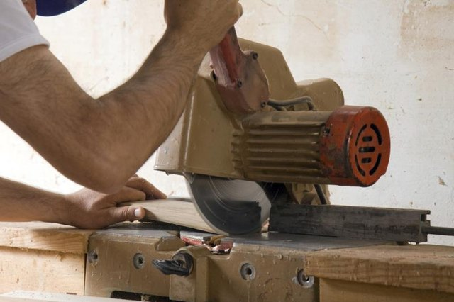 A workman uses a table saw to cut a wood board