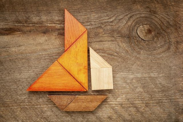 A tangram puzzle in the form of a sailboat, laying on a wooden table.
