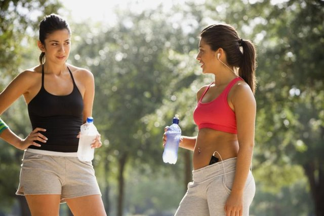 Two women holding water bottles while on exercise break.