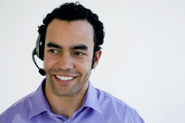Close-up of a computer technician speaking into a headset.