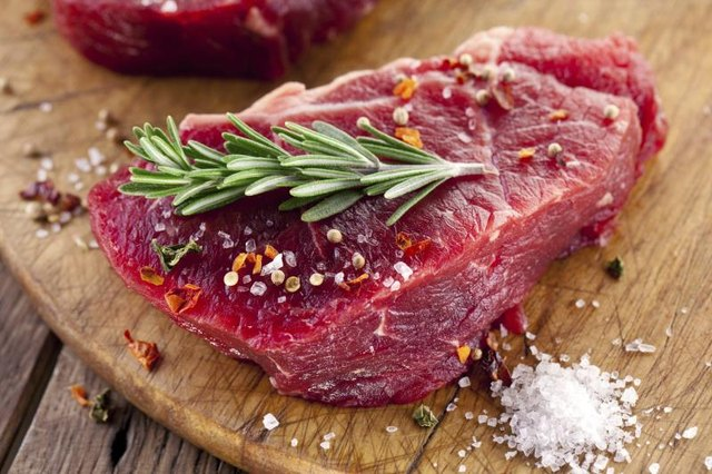 Raw beef steak with herbs and spices.