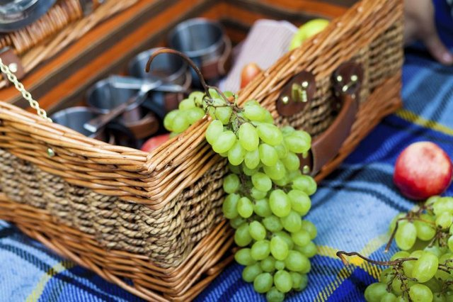 A picnic basket on a blanket filled with grapes.