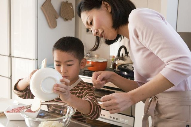 A mother helping her son add ingredients to a mixing bowl.