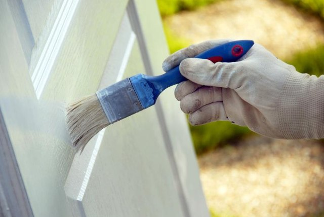 A person painting a wooden door with a brush.