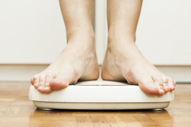 Feet standing on a bathroom scale.