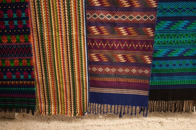 Colorful woven rugs hanging at a market.