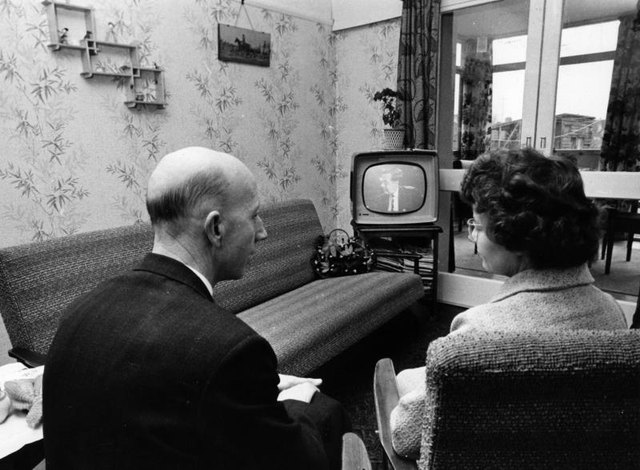 Couple watching television in living room circa 1965