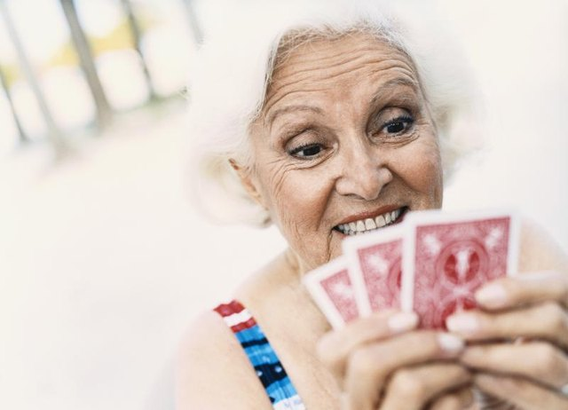 A mature woman holding playing cards.