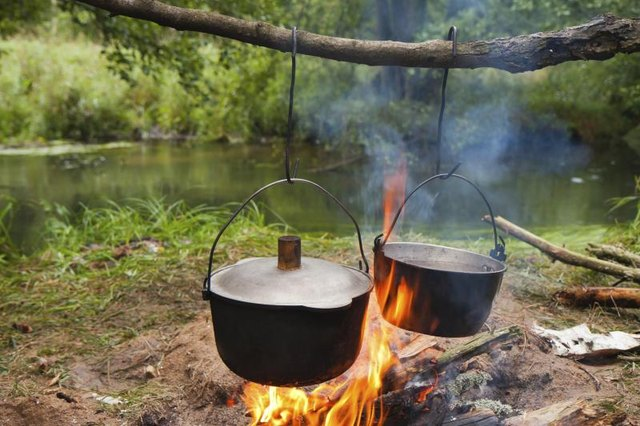 Cooking pots hang over camp fire