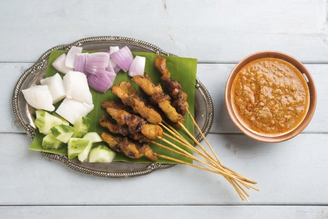 Chicken satay on skewers with a bowl of peanut sauce.