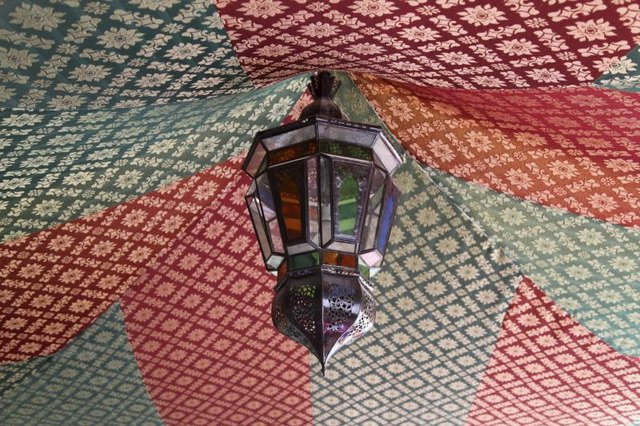 A Moroccan lamp hanging from the center of an awning.