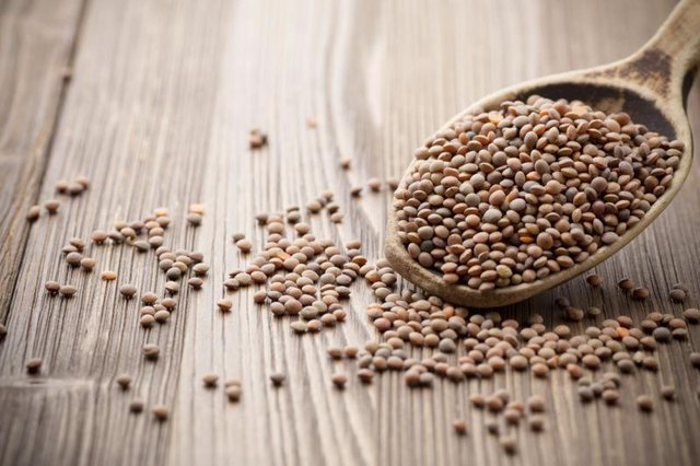 Dry lentils on a wooden spoon.