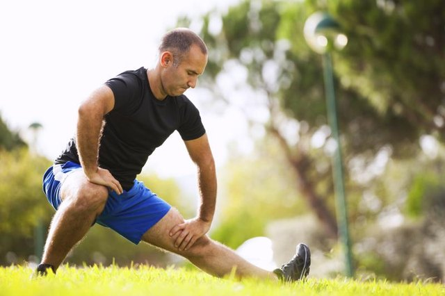 A man streches in a city park.