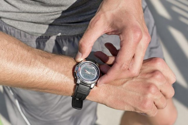 A close-up of a man looking at his watch while working out.