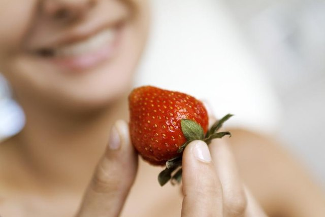A woman holding a strawberry.
