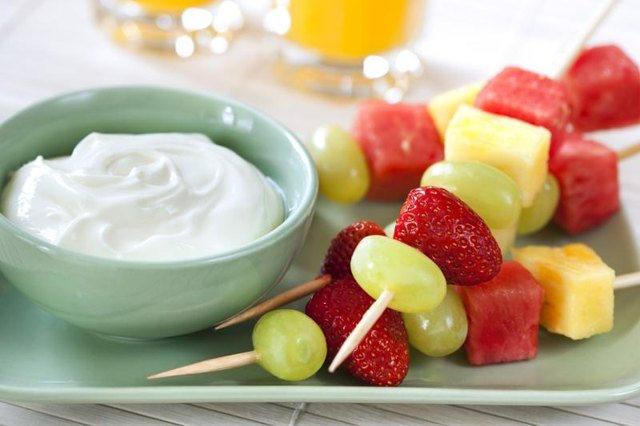 Skewers of fruit with a bowl of yogurt on the side.