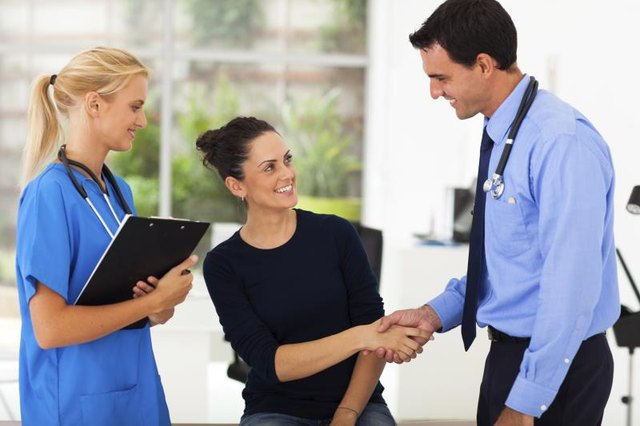 A doctor and medical assistant talk to a happy patient