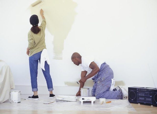 A couple painting a wall with rollers.