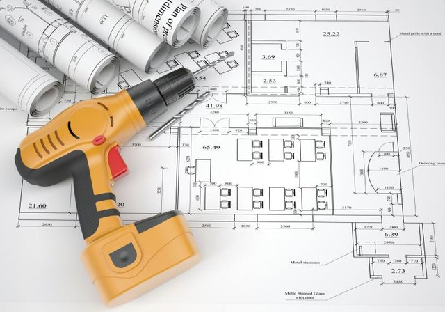 An electric screwdriver sitting on architectural plans.