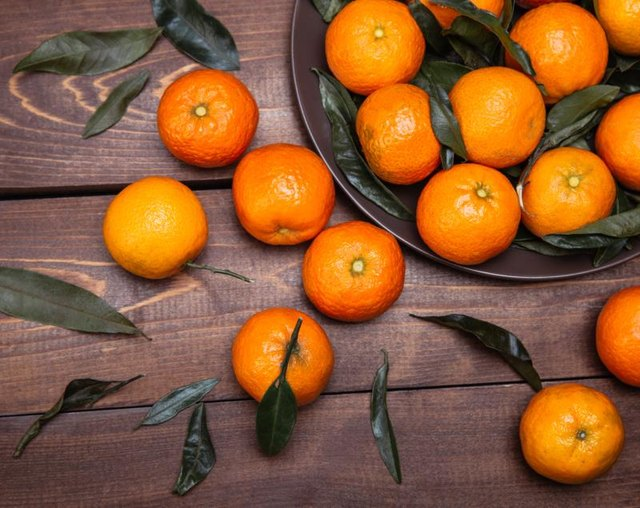 Tangerines in a bowl and on a wood table