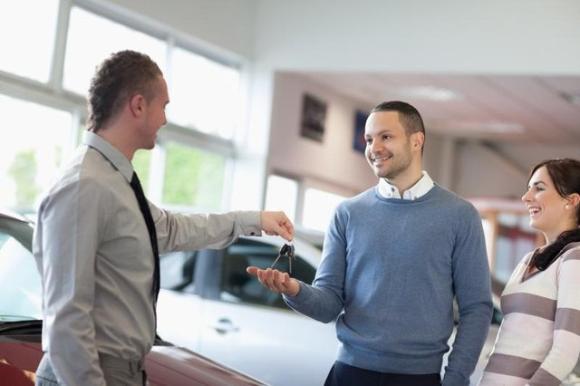 A car salesman hands keys to a young couple